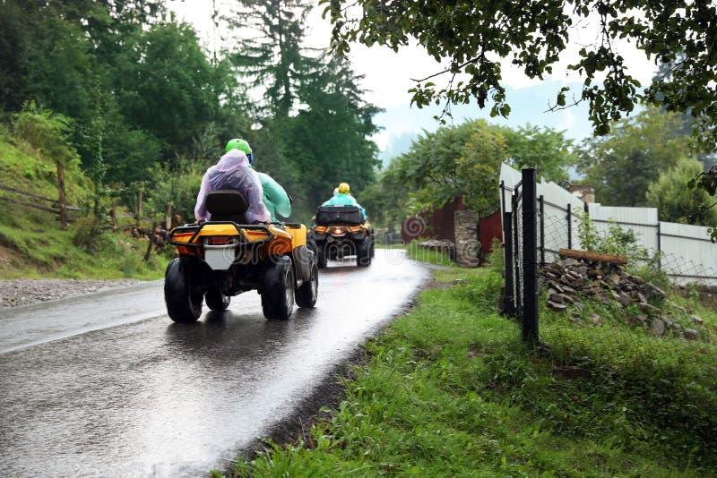 骑方形字体自行车的游人在路 免版税图库摄影