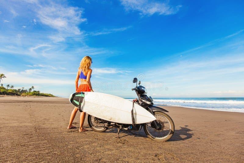 骑有冲浪板的妇女一辆摩托车 免版税库存图片