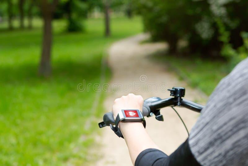 骑有smartwatch心率显示器的妇女一辆自行车 图库摄影