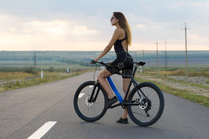 骑登山车在柏油路,骑自行车者的美丽的画象的女孩 免版税图库摄影