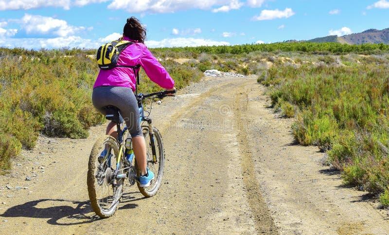 骑登山车的妇女由土一条泥泞的道路  库存照片