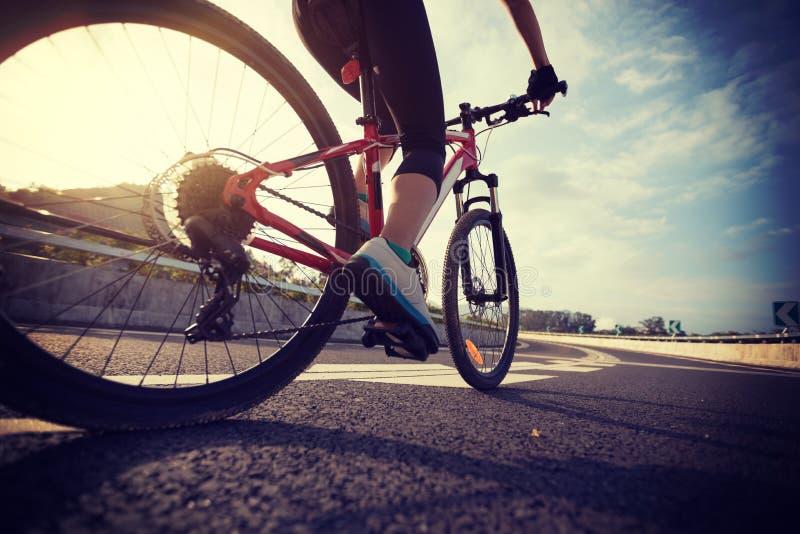 骑登山车的骑自行车者腿在高速公路 图库摄影
