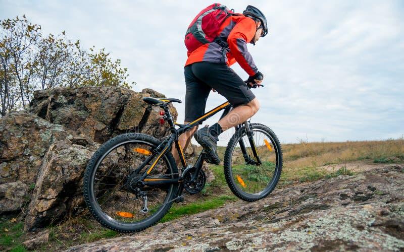 骑秋天岩石足迹的红色的骑自行车者登山车 极端体育和Enduro骑自行车的概念 免版税库存图片