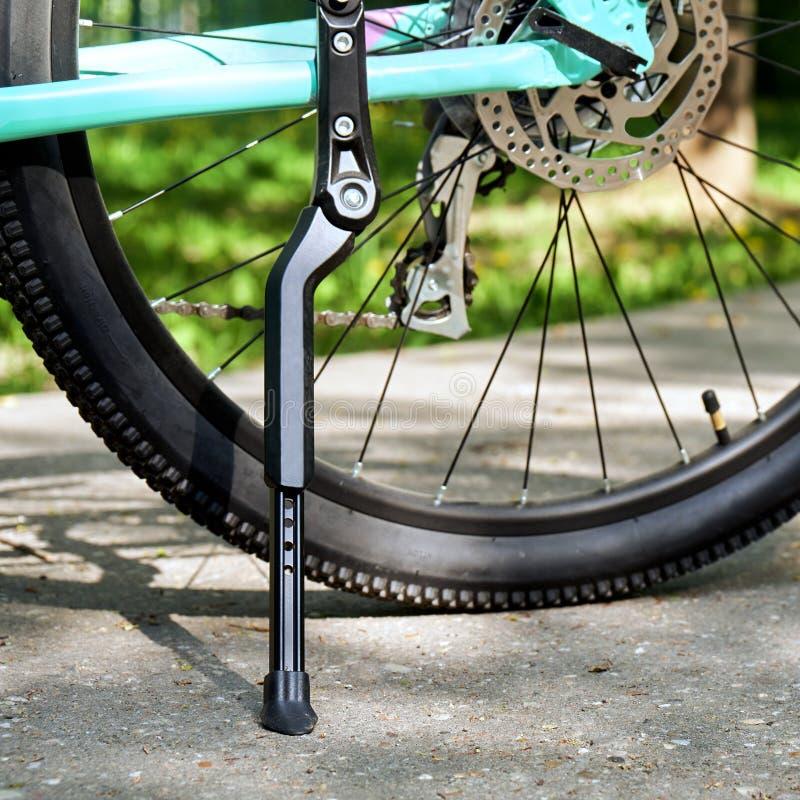 骑自行车与后方自行车车轮身分的kickstand在与绿草的沥青在背景 免版税库存图片