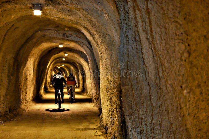 骑自行车向下入隧道的人们在山下 免版税图库摄影