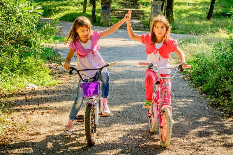 骑自行车和使用互相的两个小女孩 免版税库存照片