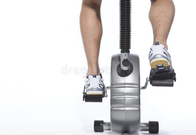 骑自行车固定式人的脚蹬谁 免版税库存图片