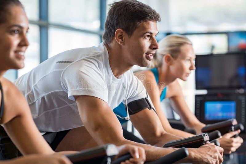 骑自行车在健身房的健身类 免版税库存照片