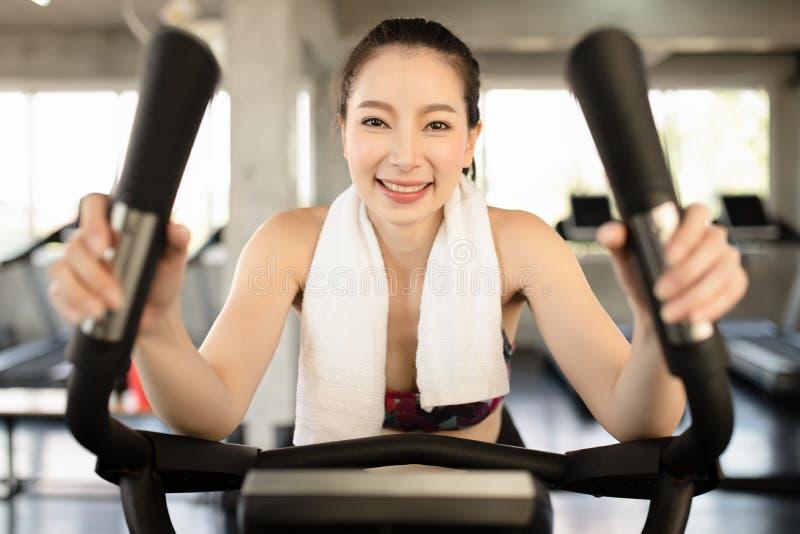 骑自行车在健身房的可爱的妇女,行使做心脏锻炼循环的自行车的腿 有训练自行车的健身房锻炼 库存图片