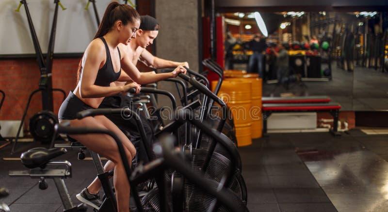 骑自行车在健身房的妇女和人,行使做心脏锻炼循环的自行车的腿 免版税库存图片