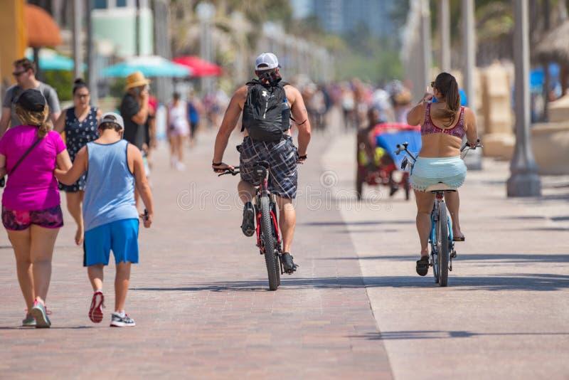 骑自行车在好莱坞海滩FL的人们 免版税库存照片