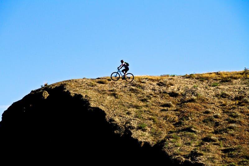 骑自行车在峭壁附近的山 免版税库存照片
