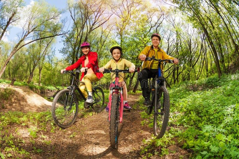 骑自行车在森林足迹的愉快的家庭山 免版税库存图片