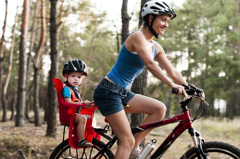 骑自行车在森林里的家庭 库存照片
