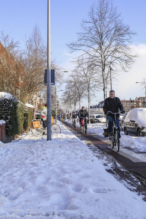 骑自行车在雪的荷兰人民 图库摄影