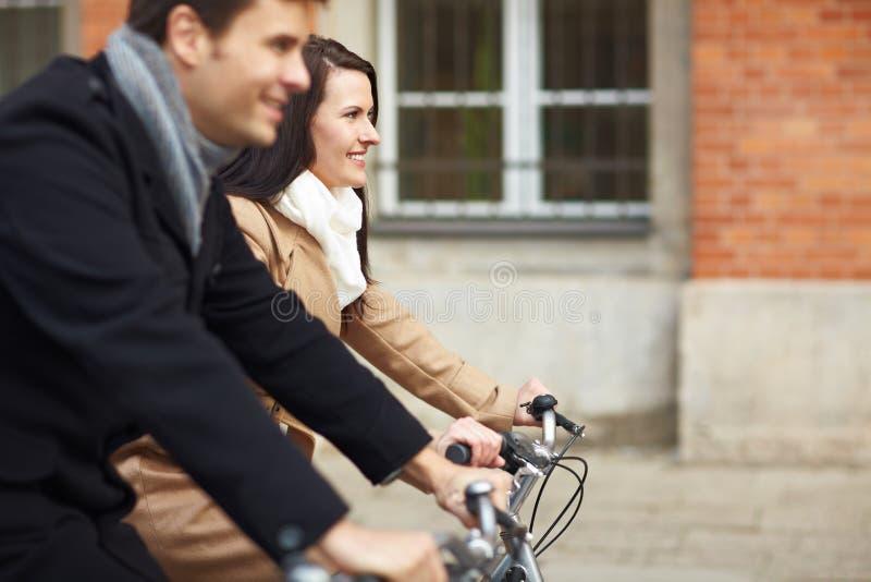 骑自行车城市夫妇骑马 库存照片