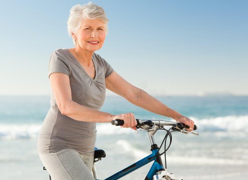 骑自行车她的高级妇女 免版税库存照片