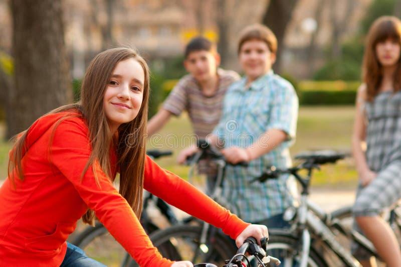 骑自行车少年的朋友 库存图片