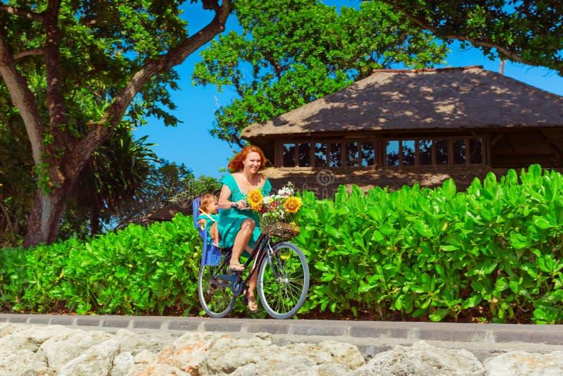 骑自行车年轻的母亲,获得与小女儿的乐趣 库存图片