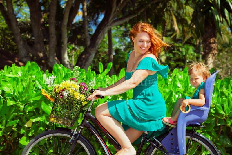 骑自行车年轻的母亲,获得与小女儿的乐趣 库存照片