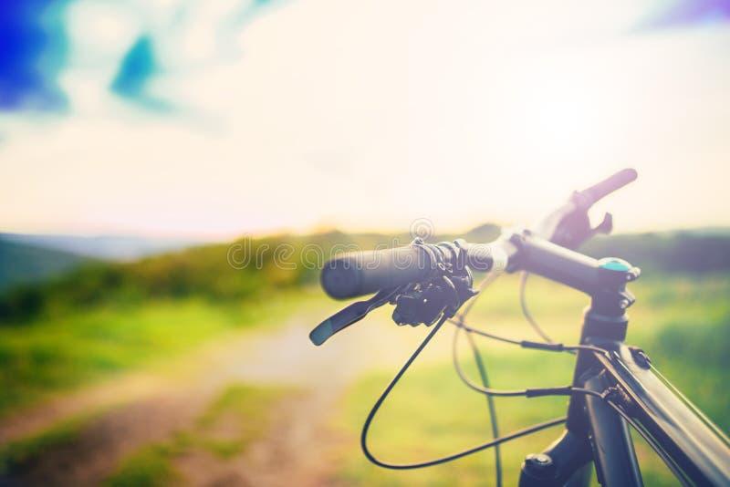 骑自行车把柄酒吧在山行迹的日落 体育活动细节  图库摄影