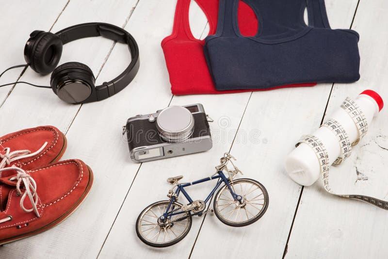 骑自行车模型,鞋子,衬衣,耳机,照相机,瓶wate 库存图片
