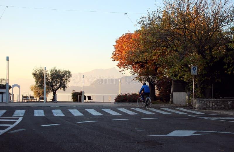 骑自行车的一个人在一条离开的街道 免版税图库摄影