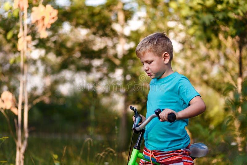 骑自行车的七岁的男孩在被弄脏的自然本底 库存照片