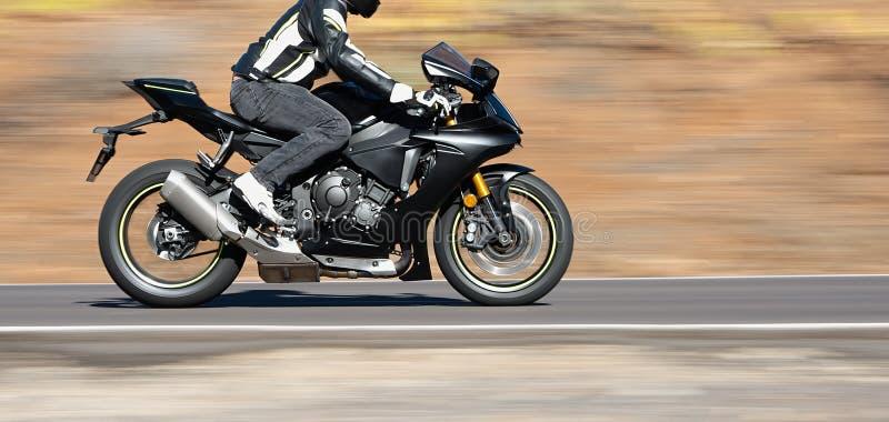 骑自行车的人一辆大功率摩托车的骑马摩托车 图库摄影