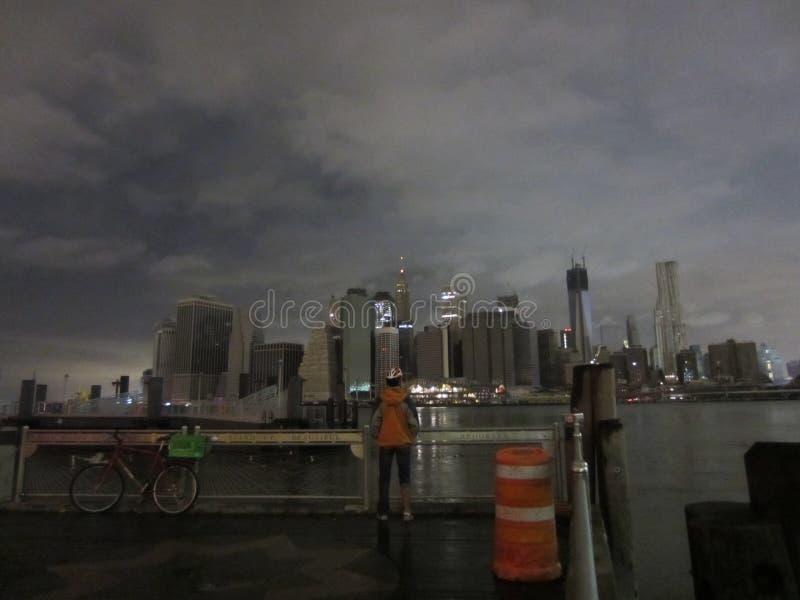 骑自行车的人和黑暗的曼哈顿 编辑类照片