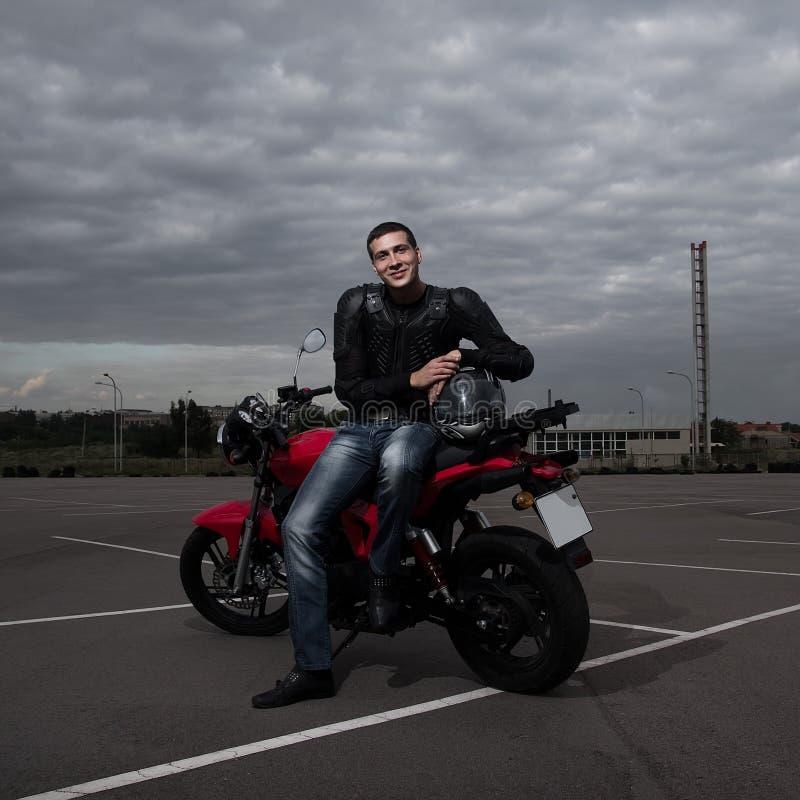 骑自行车的人和他的摩托车 免版税库存图片