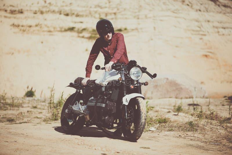 骑自行车的人在沙漠上他的老习惯自行车 葡萄酒摩托车 免版税库存照片