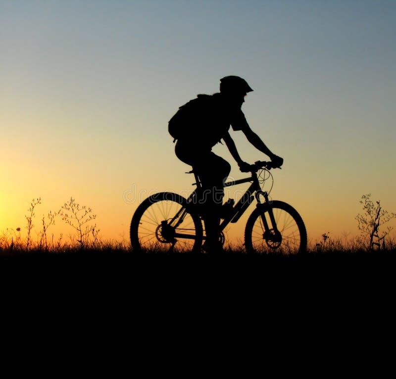 骑自行车的人女孩山剪影 免版税库存图片