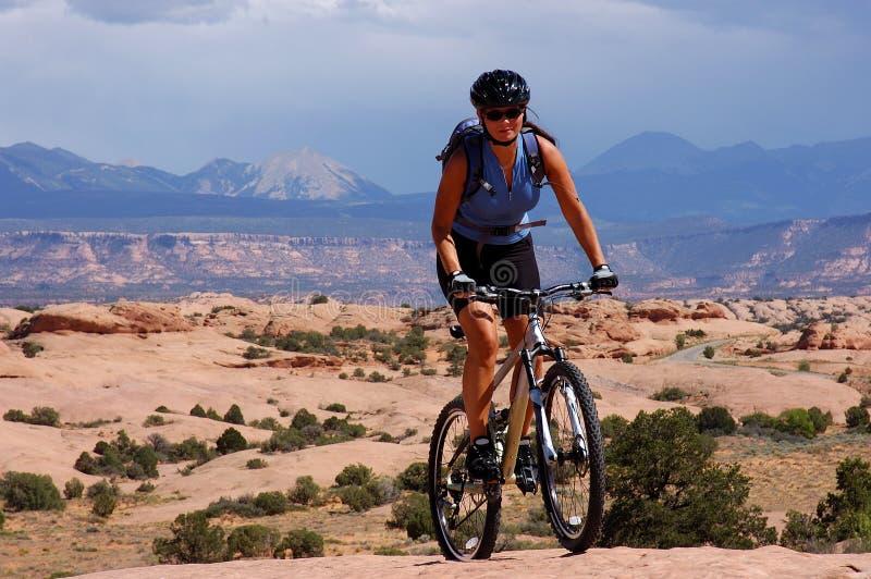 骑自行车的人女性山 库存照片