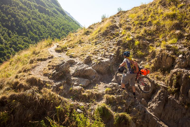 骑自行车的人推挤他的自行车在高高加索山脉 免版税库存照片