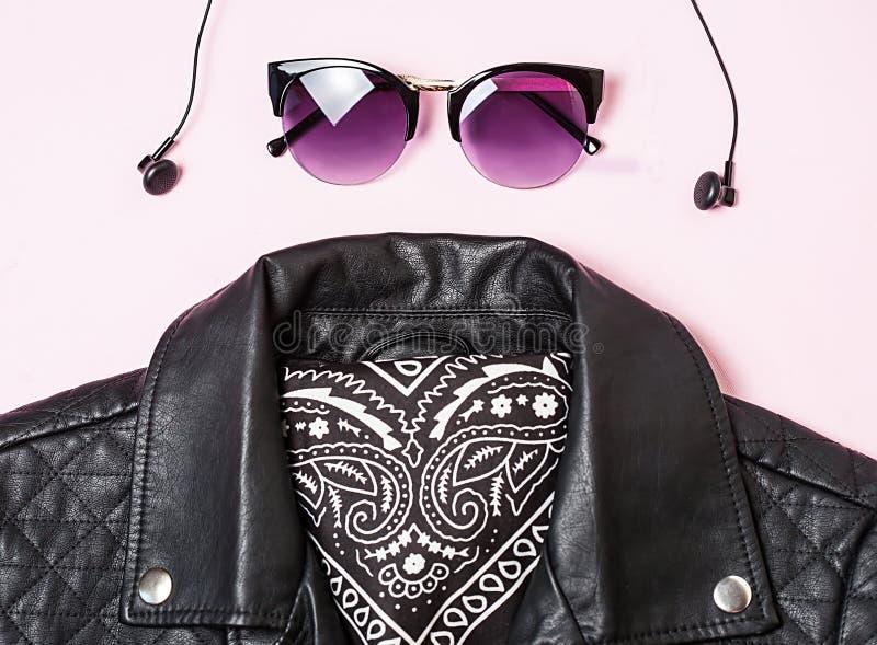 骑自行车的人有耳机的夹克和妇女太阳镜在桃红色背景 供选择的时尚集合 平的位置,顶视图 库存照片