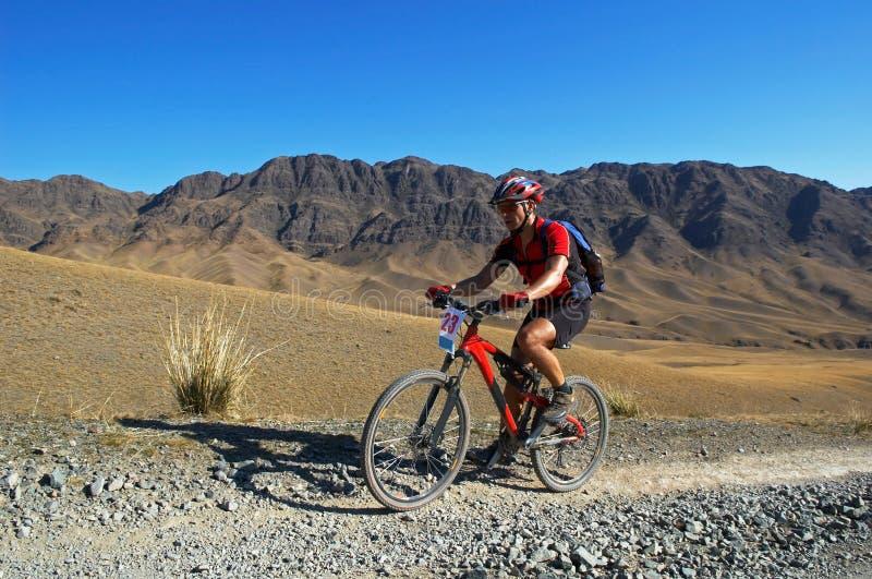 骑自行车的人沙漠山赛跑 免版税库存照片