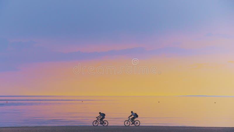 骑自行车的人沿海滩的剪影骑马在自行车运动的公司团体的日落自行车户外成功的朋友 免版税库存照片