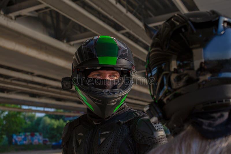 骑自行车的人男人和妇女画象盔甲的看彼此 摩托车爱概念 极其车手 免版税库存图片