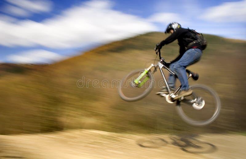 骑自行车的人跳的山 免版税图库摄影