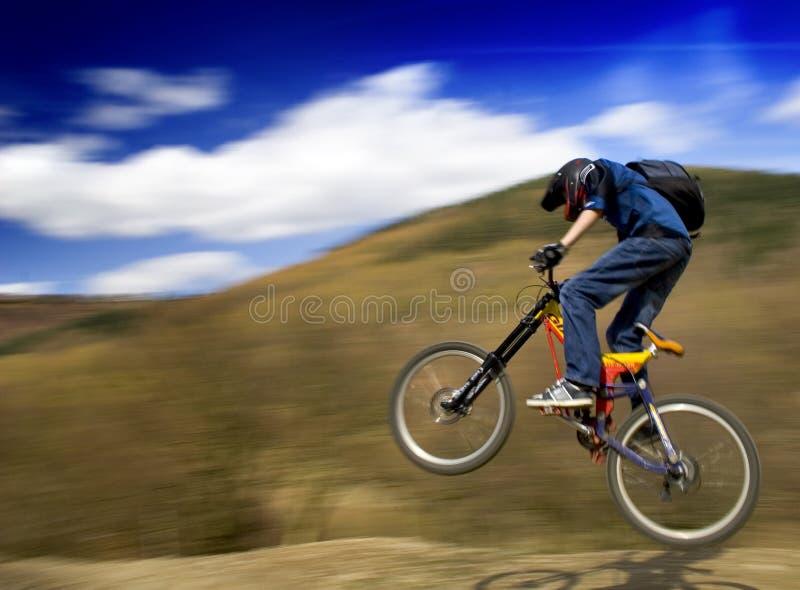 骑自行车的人跳的山 库存图片