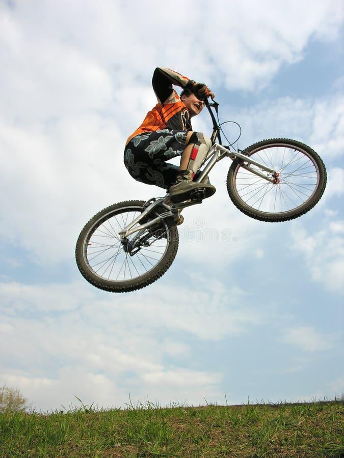 骑自行车的人跳的山 免版税库存照片