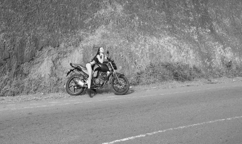 骑自行车的人题材:有摆在与motorbik的性感的身体的美丽的妇女 库存照片