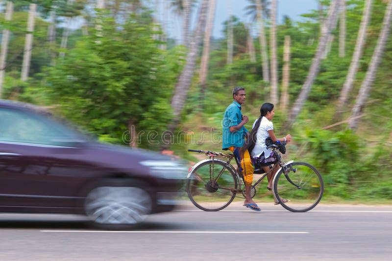 骑自行车的夫妇在地方路 免版税图库摄影