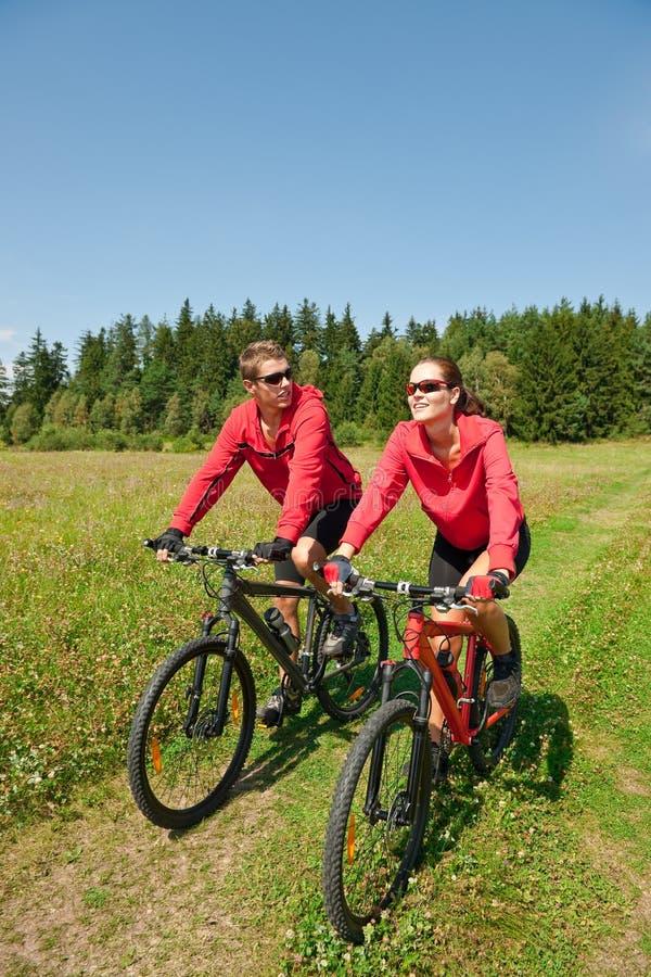 骑自行车的夫妇本质嬉戏春天 库存图片