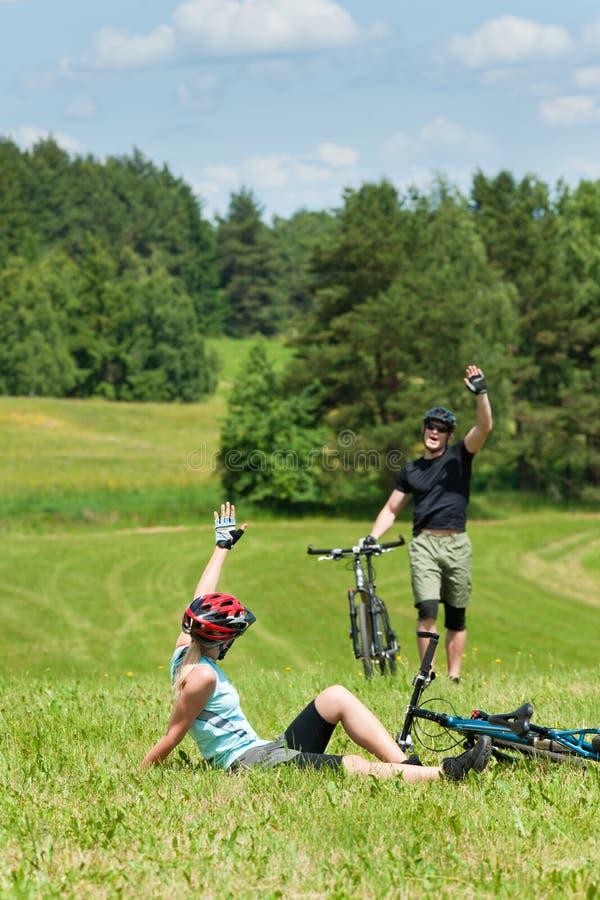 骑自行车的夫妇问候草甸山体育运动 库存照片