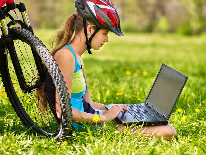 骑自行车的女孩佩带的盔甲循环的坐在自行车手表膝上型计算机附近 免版税库存图片
