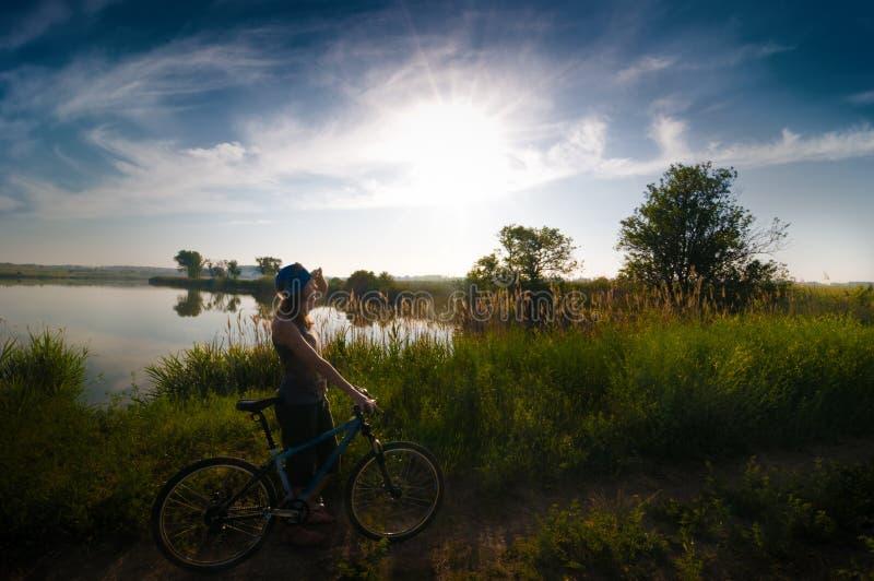 骑自行车的女孩日出 免版税库存照片