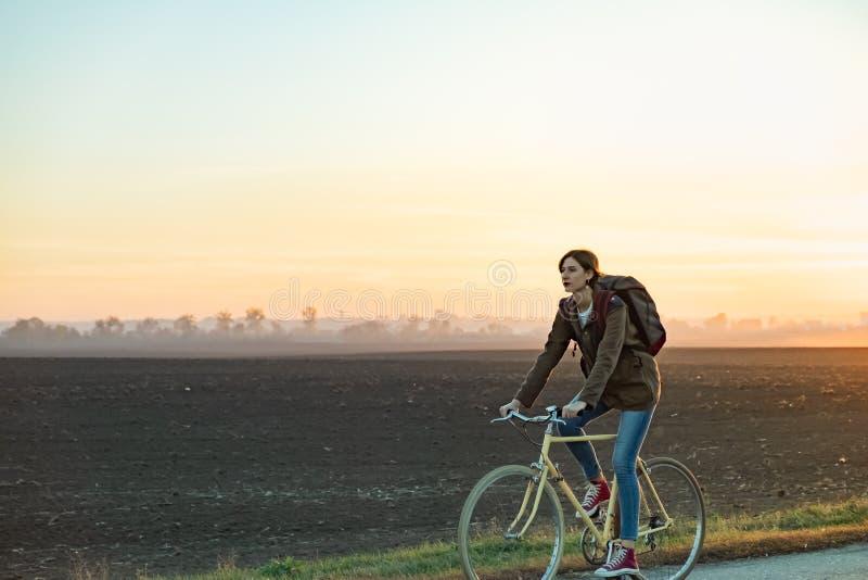 骑自行车的女性通勤者在农村的镇外面 年轻w 免版税库存照片