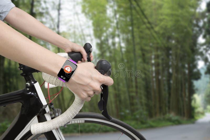 骑自行车的妇女递佩带的健康传感器巧妙的手表 库存照片